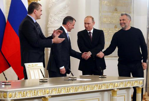 Russian president Vladimir Putin shakes hands with parliamentary speaker Vladimir Konstantinov and Sevastopol Mayor Alexei Chaliy, while Crimea's Prime Minister Sergei Aksyonov looks on, following a signing ceremony at the Kremlin in Moscow to make Crimea a part of Russia.