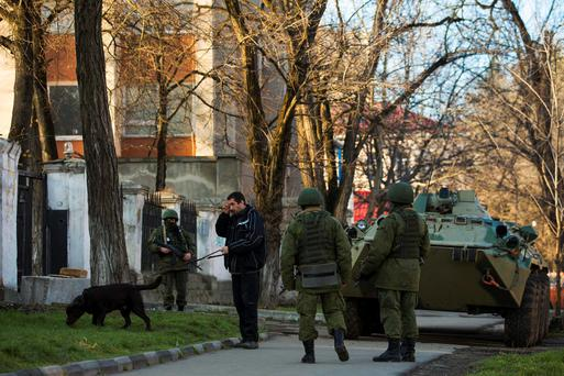Armed men, believed to be Russian soldiers, stand guard outside a Ukrainian military base in Simferopol March 19, 2014.