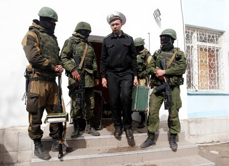 A Ukrainian naval officer (C) passes by armed men, believed to be Russian servicemen, as he leaves the naval headquarters in Sevastopol