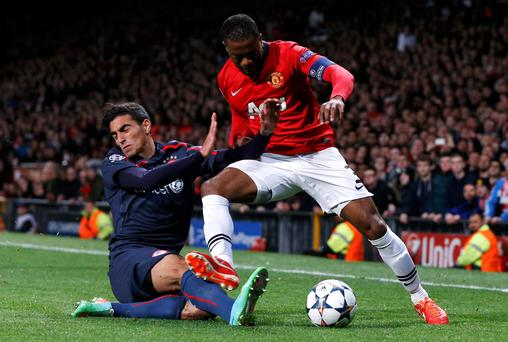 Manchester United's Patrice Evra (R) challenges Olympiakos' Nikos Vergos during their Champions League soccer match at Old Trafford in Manchester, northern England, March 19, 2014. REUTERS/Phil Noble (BRITAIN - Tags: SPORT SOCCER)
