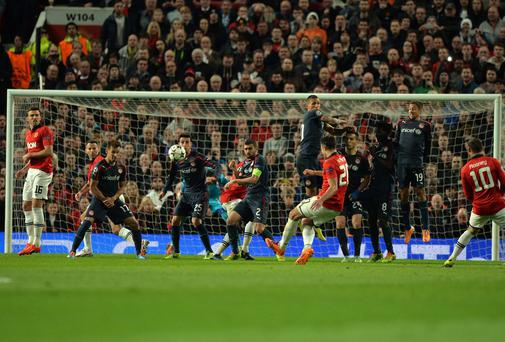 Manchester United's Dutch striker Robin van Persie shoots to score his third against Olympiakos at Old Trafford