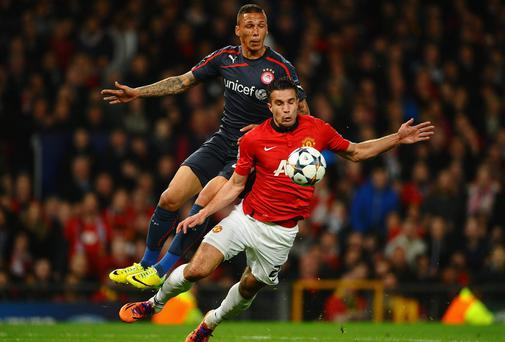 Manchester United forward Robin van Persie is fouled in the penalty box by Olympiacos' Jose Holebas