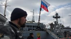 A Russian flag is raised aboard a Ukrainian navy ship that is next to the Ukrainian corvette Pridniprovya, right, in Sevastopol, Crimea. Pro-Russian crowds seized two Ukrainian warships Thursday.