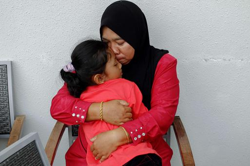 Rosila Abu Samah, 50, and her daughter Kaiyisah Selamat, 8, the mother and sister of flight engineer Mohd Khairul Amri Selamat who was on board missing Malaysia Airlines flight MH370, hug each other as they await news on the missing plane.