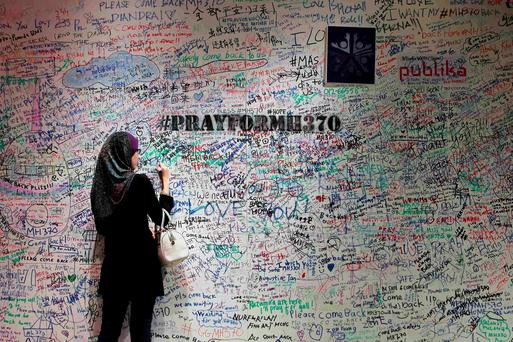 A woman writes on the message board in support of the passengers and family members of the missing Malaysia Airlines Flight MH370, at a shopping mall in Bangsar near Kuala Lumpur March 21, 2014. REUTERS/Samsul Said