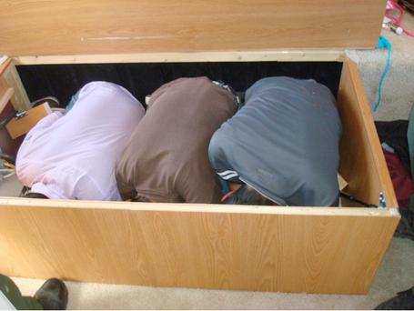 Image provided by the U.S. Department of Homeland Security shows three adult Mexican immigrants crouched in a box after being discovered in a storage compartment under the bed of a recreational vehicle near San Diego.