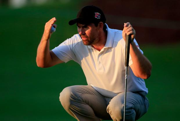 Padraig Harrington of Ireland shields his eyes from the sun as he lines up his putt for birdie