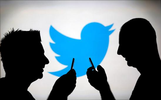 Men are silhouetted against a video screen with an Twitter logo