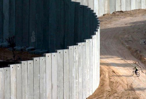THE WALL: A Palestinian boy cycles near the infamous barrier