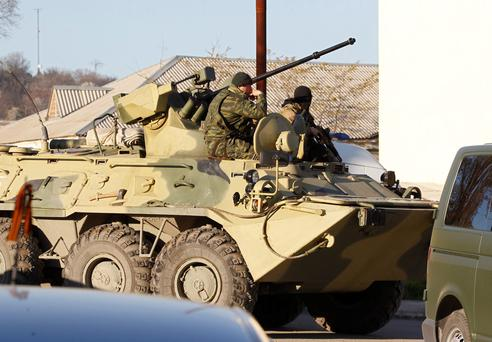 Armed men, believed to be Russian servicemen, sit in an armoured vehicle near a military base in the Crimean town of Belbek near Sevastopol March 22, 2014. Russian troops have surrounded a Ukrainian airbase in Crimea and issued an ultimatum to forces inside to surrender, the deputy commander of the base in Belbek, near Sevastopol, said on Saturday. REUTERS/Vasily Fedosenko (UKRAINE - Tags: POLITICS MILITARY)