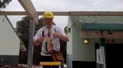 A volunteer gives the thumbs up as he works away on the Mellon Educate project at the Orangekloof primary school in Cape Town, South Africa