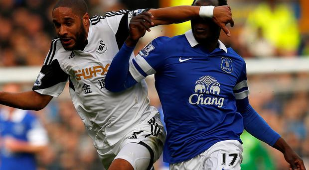 Everton's Romelu Lukaku (R) is challenged by Swansea City's Ashley Williams during their English Premier League soccer match at Goodison Park