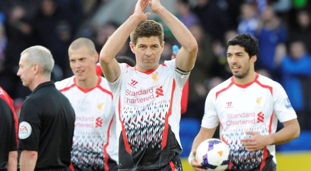 Liverpool's captain Steven Gerrard (C) claps while flanked by Luis Suarez (R), holding the match ball