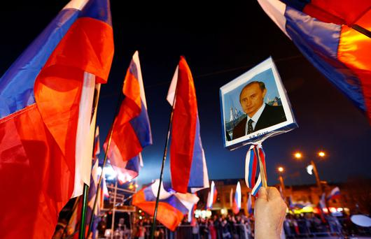 A woman holds a portrait of Russia's President Vladimir Putin during celebrations on the main square ofthe Crimean city.