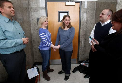 Elizabeth Gardiner (L) and Stephanie Citron hold hands as a woman (R) officiating their wedding ceremony reads the marriage vows from her cell phone in the hallway of the Oakland County Courthouse in Pontiac, Michigan. Michigan's ban on same-sex marriage violates the U.S. Constitution and must be overturned, a federal judge ruled on Friday