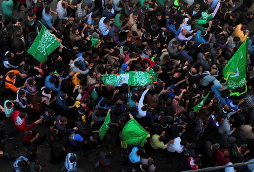 Palestinians shout slogans as they carry the body of Hamas militant Hamza Abu Alhija in the West Bank refugee camp of Jenin