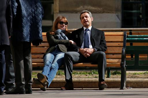 Former French President Nicolas Sarkozy sits on a bench with his wife and singer Carla Bruni-Sarkozy after voting