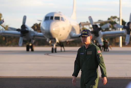 Japanese Commander Hidetsugu Iwamasa walks along the tarmac at Royal Australian Air Force Pearce Base after his P-3C Orion aircraft from Japan Maritime Self-Defense Force arrived to help with search operations for the missing Malaysia Airlines Flight MH370, in Perth