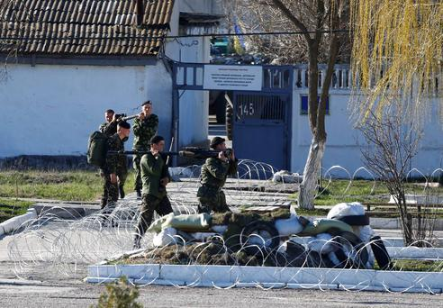 Ukrainian marines carry weaponry at a Ukrainian marine base in the Crimean port city of Feodosia