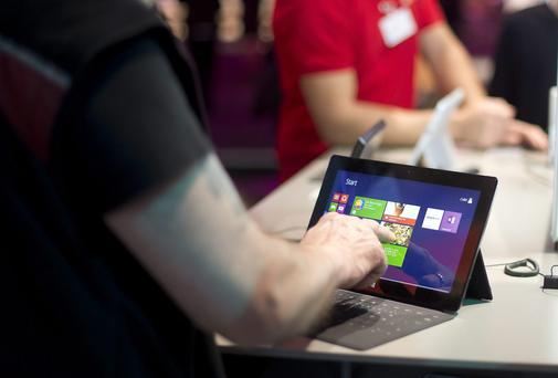 A Visitor touches a surface tablet at the Microsoft stand at the 2014 CeBIT technology Trade fair