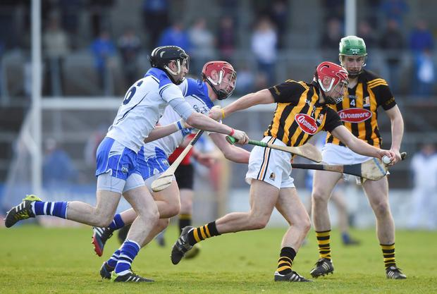 Cillian Buckley, supporter by Joey Holden, Kilkenny, in action against Ray Barry and Pauric Mahony, Waterford