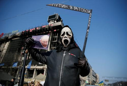 Participant hold a sign depicting Russian President Vladimir Putin as he attends an anti-war rally at Independence Square in Kiev