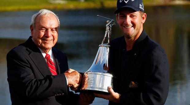 Arnold Palmer congratulates Matt Every of the United States as he celebrates with the trophy after winning the Arnold Palmer Invitational