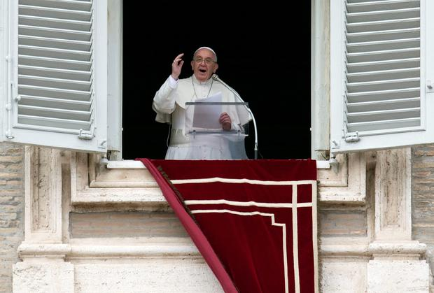 Pope Francis delivers his blessing during the Angelus noon prayer he celebrated from the window of his studio overlooking St Peter's Square, at the Vatican