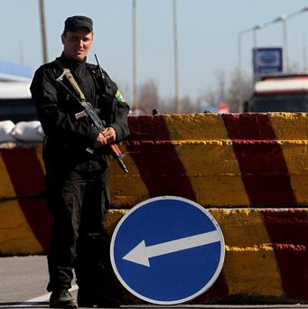 Ukrainian servicemen stand on guard at a checkpoint near the town of Armyansk in Kherson region adjacent to Crimea