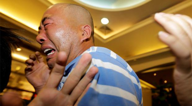 Relatives of passengers aboard Malaysia Airlines MH370 react to news that no one survived from the flight