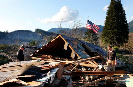 Brian Anderson, left, and Coby Young search through the wreckage of a home belonging to the Kuntz family Sunday, March 23, 2014, near Oso, Wash
