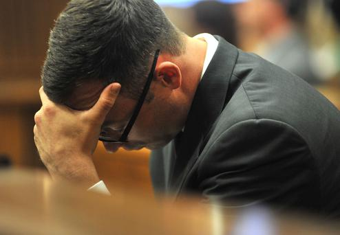 Oscar Pistorius holds his head in his hands as he listens to evidence being given in court in Pretoria, South Africa today