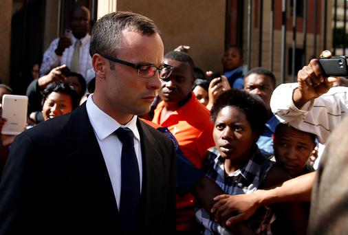 Olympic and Paralympic track star Oscar Pistorius (L) leaves after his trial for the murder of his girlfriend Reeva Steenkamp, at the North Gauteng High Court in Pretoria, March 24, 2014. Photo: Reuters.