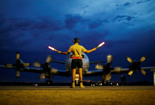 A ground controller guides a Royal Australian Air Force AP-3C Orion on the tarmac upon its return from a search for Malaysian Airlines flight MH370 over the Indian Ocean, at RAAF Base Pearce north of Perth