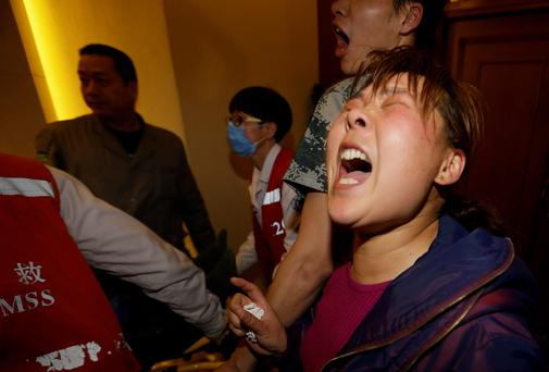 A family member of a passenger aboard Malaysia Airlines MH370 shouts at journalists after watching a television broadcast of a news conference, at the Lido hotel in Beijing