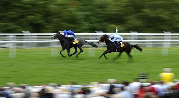 Richard Hughes riding Toormore (R) on their way to winning The Veuve Clicquot Vintage Stakes at Goodwood racecourse on July 31, 2013