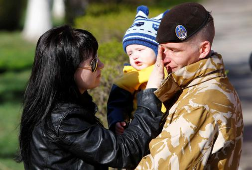 A Ukrainian marine speaks with his wife and son before departing Crimea outside a Ukrainian military base in the Crimean port city of Feodosia