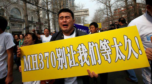 A relative of a passenger aboard Malaysia Airlines MH370 cries as he marches along a street with other family members during a protest rally in Beijing