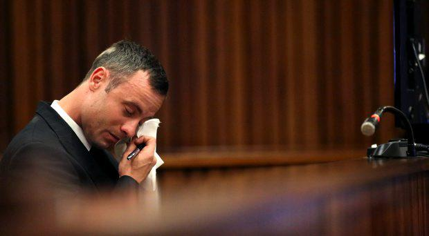 Oscar Pistorius wipes tears from his face as he sits in the dock during his trial for the murder of his girlfriend Reeva Steenkamp