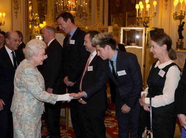 Queen Elizabeth II meets One Direction's Niall Horan (2nd right) at a reception for the Irish community at Buckingham Palace, London