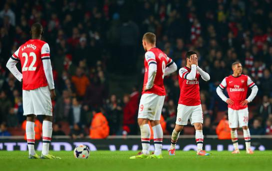 A dejected Mikel Arteta of Arsenal holds his head in his hands after Mathieu Flamini of Arsenal (not pictured) scored an own goal in the final minutes during the Barclays Premier League match between Arsenal and Swansea