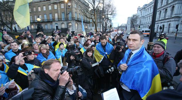 Ukrainian MP Vitaly Klitschko, leader of the Ukrainian Democratic Alliance for Reform party (UDAR), right, drapes a Ukrainian flag over his shoulders as he speaks to demonstrators demanding action against Russia following a meeting with British prime minister David Cameron and foreign secretary William Hague, at 10 Downing Street yesterday.
