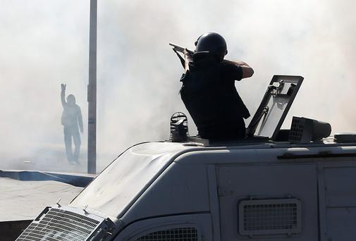 A special forces police officer fires rubber bullets as a protester raises his hand during a demonstration at the front of Cairo University. One person was killed near Egypt's Cairo University on Wednesday when protesters supporting ousted President Mohamed Mursi clashed with security forces, a health ministry official told Reuters. The protesters were demonstrating against a court ruling earlier this week condemning more than 500 alleged Muslim Brotherhood supporters to death. Reuters