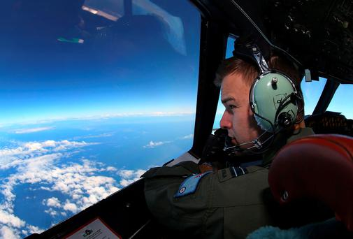 Flight Lieutenant Russell Adams looks out from the cockpit of a Royal Australian Air Force (RAAF) AP-3C Orion aircraft while searching for the missing Malaysia Airlines Flight MH370 over the southern Indian Ocean. Reuters