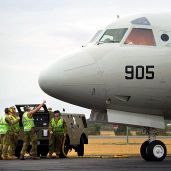 Ground staff assist a Republic of Korea Navy (ROKN) P-3C Orion maritime patrol aircraft after it arrived at the Royal Australian Air Force (RAAF) Base Pearce, located north of Perth, to participate in the search for missing Malaysia Airlines flight MH370