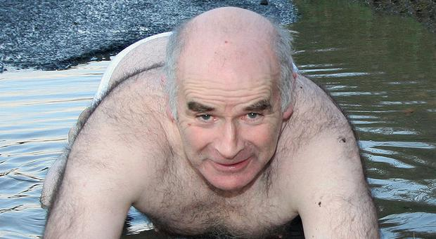 Cavan Pothole Terror Martin Hannigan has been banned by Cavan District Court from painting on the roads, Martin seen here swimming in a pothole in Cootehill during his campaign which lasted nearly 25 years. Photo: Lorraine Teevan
