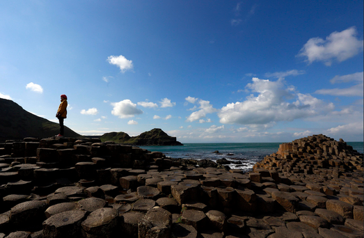 A woman poses for a picture on the rocks at the Giant's Causeway situated on the north coast of Northern Ireland. Photo: Reuters/Cathal McNaughton
