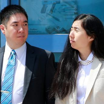Matthew (L) and Grace Huang, a U.S. couple who were accused of murdering their adopted daughter Gloria, stand outside the entrance of the Court of First Instance after their trial in Doha