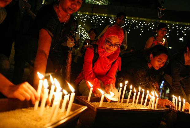People place their candles after a candlelight vigil for the passengers of the missing Malaysia Airlines MH370 in central Kuala Lumpur yesterday