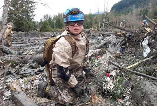 Air Force Master Sergeant Eva Mayberry and other volunteers remove debris by hand in an effort to find missing persons following the deadly mudslide in Oso, Washington